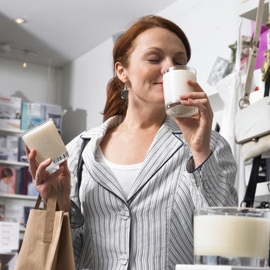 woman smelling candles while shopping downtown shopping