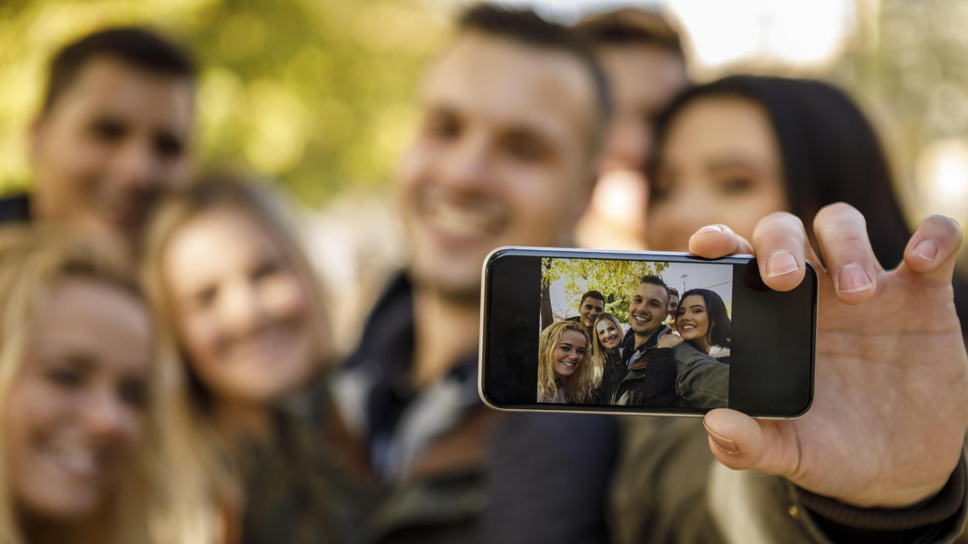 group of friends taking selfie outdoors