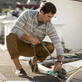 man tying boat line to cleat on dock