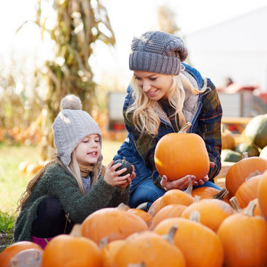 mother and daughter picking pumpkins